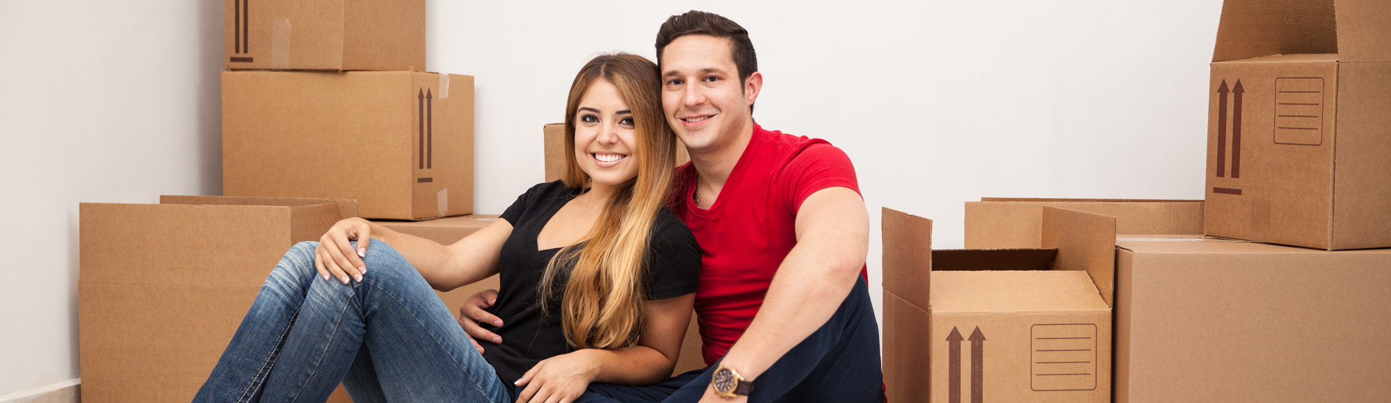 Cute Hispanic young couple moving to their new home and unpacking